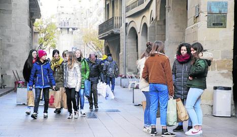 Joves amb bosses de compres, ahir al matí a l'Eix Comercial.
