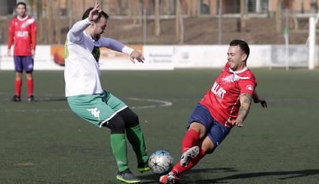 Un jugador de l'equip local i un del visitant es disputen la pilota.