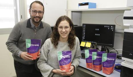 Elias Daura i una investigadora de Biomeb mostren els sobres amb què es ven la fibra.