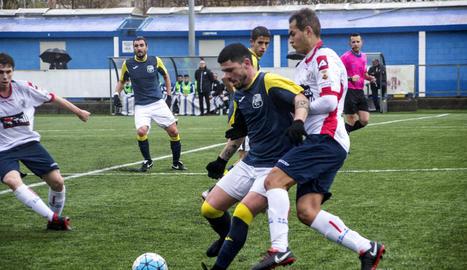 Un jugador del Borges Blanques protegeix la pilota davant la pressió d'un del Sant Ildefons.