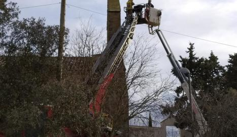 Moment en què els bombers accedeixen a la cistella per rescatar l'operari (esq.) i taca d'oli a la façana de l'església (dr.).