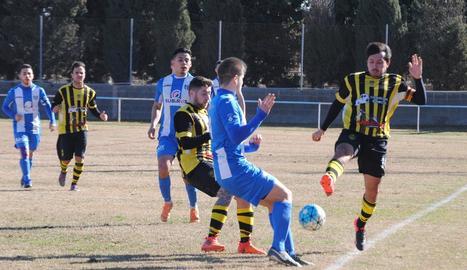 Jugadors dels dos conjunts disputen una pilota dividida en una acció del partit.