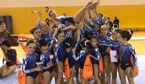 Les gimnastes del Club Gimnàstic FEDAC Lleida aixequen Àngela Mora després de participar en el Torneig d'Esplugues.