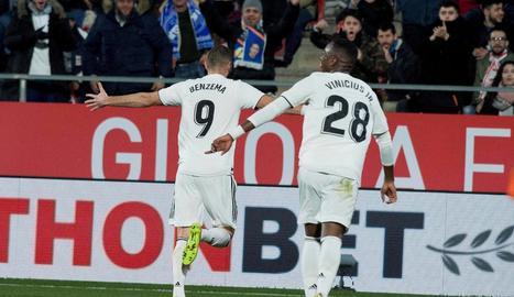 Benzema, perseguit per Vinicius, celebra un dels dos gols que va marcar ahir a Girona.