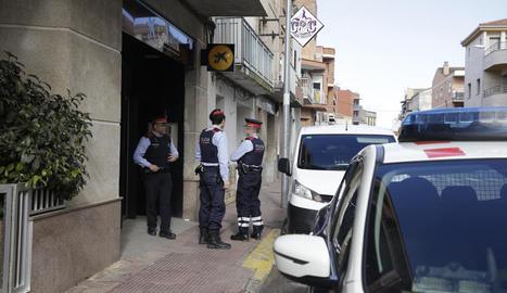 Mossos, ahir al migdia, custodiant l'oficina bancària assaltada.