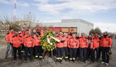 """Foto de família dels bombers voluntaris, ahir amb una corona amb el missatge """"model de bombers, descansa en pau""""."""