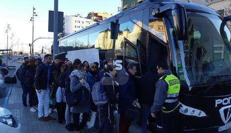 Instant en què un grup de viatgers puja a un dels autobusos que va facilitar Renfe després de l'avaria.