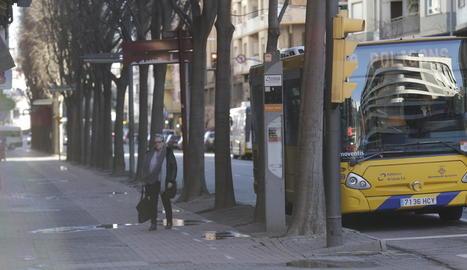 Una usuària de l'autobús baixa creuant el carril bici.