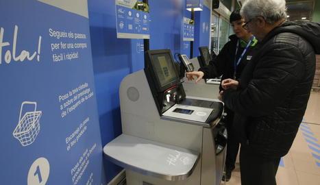 Una empleada explica com funciona la caixa d'autopagament.