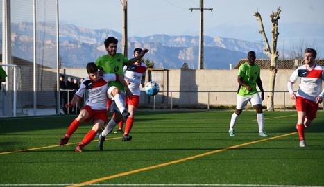 Un jugador de l'Alpicat colpeja la pilota davant la pressió d'un rival.