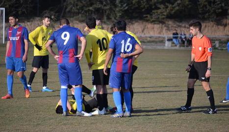 Un jugador lesionat del Juneda és envoltat per diversos companys i rivals en presència de l'àrbitre del partit.