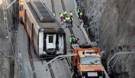 Operaris treballant ahir un dels dos combois implicats en l'accident.