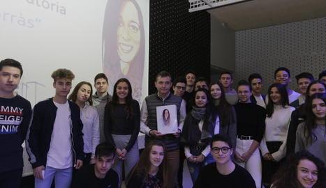 Alumnes i el director del Montsuar, amb el llibre i davant d'una imatge de Núria Borràs.
