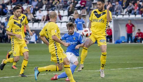 Fernando Cano és frenat per un defensa del Badalona dins de l'àrea, en una acció atacant del Lleida.