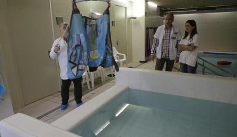 A l'esquerra, pacients fent ahir exercicis de rehabilitació i, a la dreta, una grua que permetrà ajudar usuaris a entrar a la piscina.