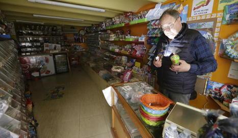 Un comerciant de l'Eix utilitza el llum del seu telèfon mòbil durant l'apagada d'ahir.