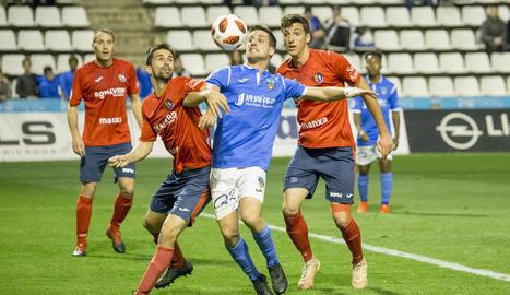Juanto Ortuño lluita amb un jugador de l'Olot en una acció del partit d'ahir.