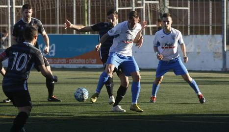 Un jugador del Mollerussa prova de mantenir la possessió de la pilota davant d'un defensa rival.