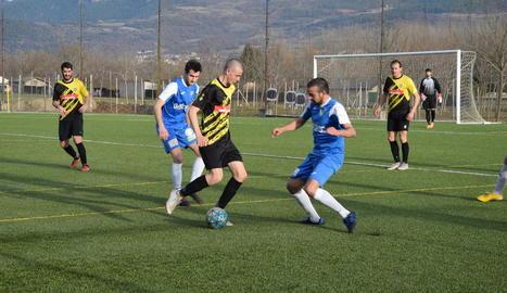Un jugador del Rialp manté la possessió de la pilota davant la persecució de dos rivals.