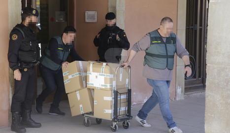 Agents de la Guàrdia Civil s'emporten de l'ajuntament d'Almacelles caixes amb documents.