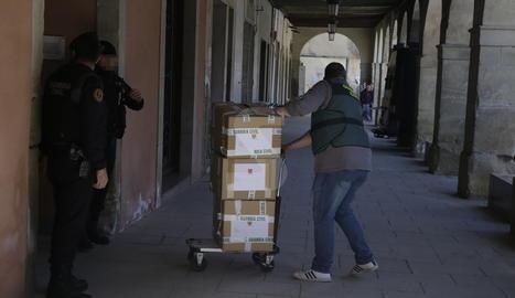 Un agent de la Guàrdia Civil treu caixes amb documents de l'edifici de l'ajuntament d'Almacelles.