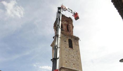 Redueixen i netegen un niu de cigonya de l'església de la Granja d'Escarp