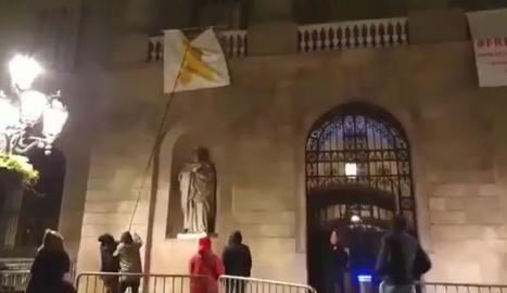 Un grup de persones despenja el llaç groc de l'ajuntament de Barcelona