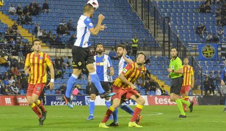 Un defensa de l'Hèrcules rebutja la pilota davant de Pedro Martín.