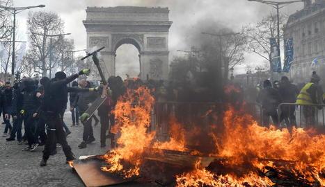 Els Armilles Grogues munten barricades i fogueres davant de la policia als Camps Elisis.