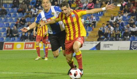 Juanto Ortuño avança amb la pilota agafat per un jugador de l'Hèrcules.