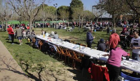 Els voluntaris reparteixen racions de la gran cassola que es va cuinar al parc del Graó.