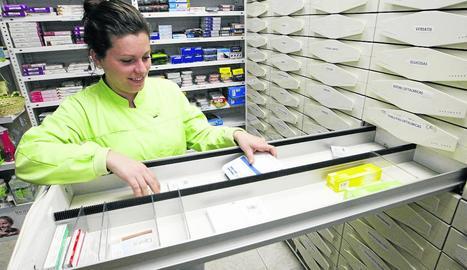 Una empleada d'una farmàcia a Pardinyes mostra els calaixos buits de medecines.