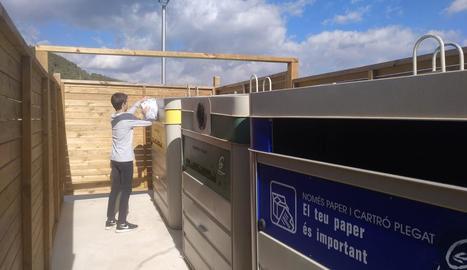 Un nen diposita escombraries als contenidors de Tarrés.