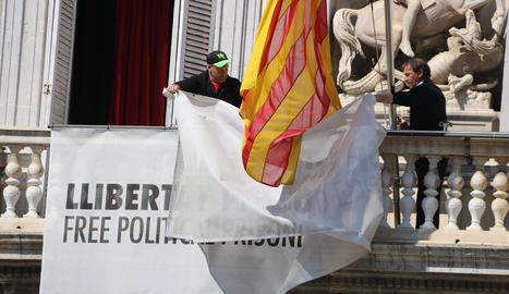 Dos treballadors de la Generalitat retiren els llaços del Palau