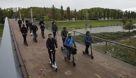 Usuaris de patinets elèctrics circulant per una passarel·la.