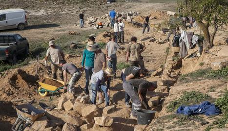 Voluntaris treballant ahir en la conservació de marges de pedra seca a Castellserà.