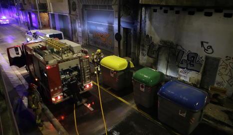 Bombers sufocant divendres a la nit un incendi que va afectar tres contenidors a Lluís Roca.