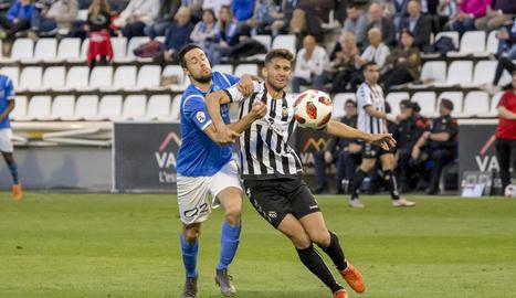 Pedro Martín forceja amb un jugador del Castelló per atrapar la pilota.