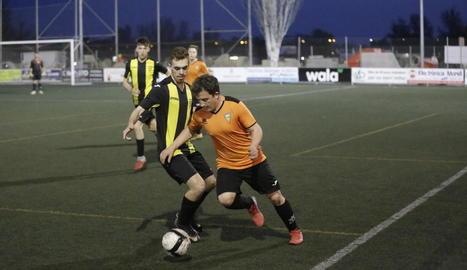 Un jugador de l'equip local i un altre del visitant es disputen la pilota.