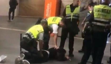 El jove, a terra, amb diversos vigilants de seguretat al costat.