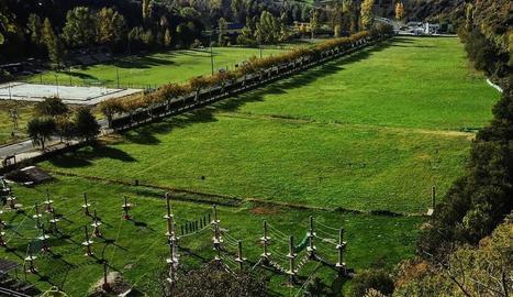 La pista esportiva de ciment, a l'esquerra, i el seu entorn dels afores del poble de Rialp.