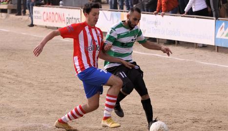 Un jugador del Verdú intenta mantenir la possessió de la bola davant la presència d'un del Pobla.