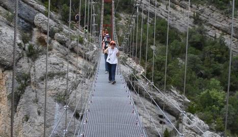 Excursionistes creuant la passarel·la de Mont-rebei.