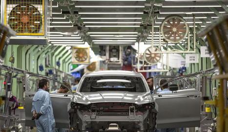 Diversos treballadors inspeccionen una carrosseria després de passar per la zona de pintura.