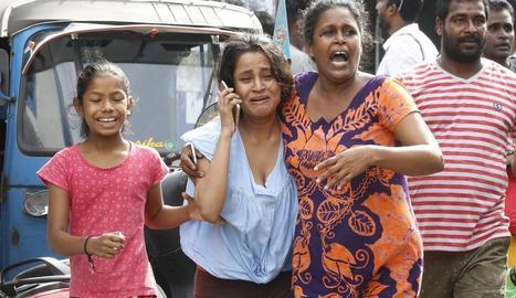 Diverses persones corren per posar-se fora de perill mentre les autoritats evacuen els voltants de l'església de Sant Antoni, a Colombo.