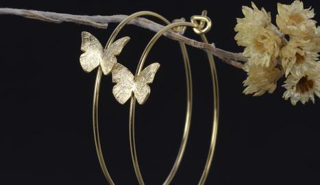 or i plata. Solitari amb turmalina talla navette, muntada en or i plata rodiada. A sota, Aros Vola, en plata banyada en or.