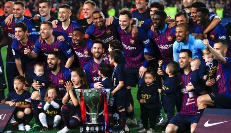 La plantilla del FC Barcelona posa amb el trofeu de la Lliga que aquesta temporada va ser entregat al campió el mateix dia en què va guanyar el títol.