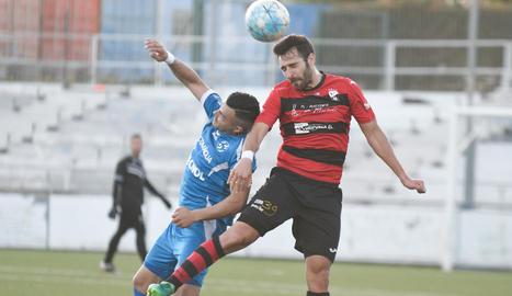 Un jugador de l'EFAC Almacelles guanya a un rival la disputa d'una pilota aèria.