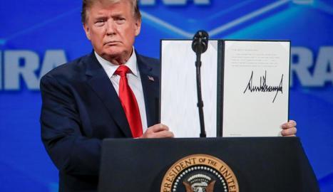 Donald Trump mostra la seua decisió firmada.