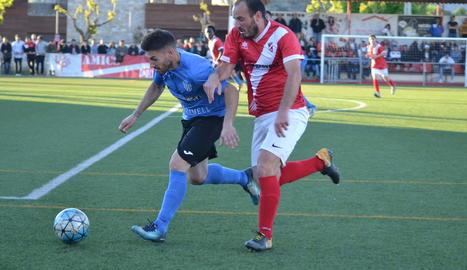 Un jugador de l'Alcarràs condueix la pilota davant la pressió d'un rival.